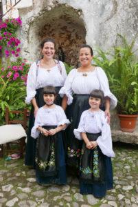 Elisa und Alessia mit ihren Töchtern Aice und Luzia in traditionellen Trachten in Olieni