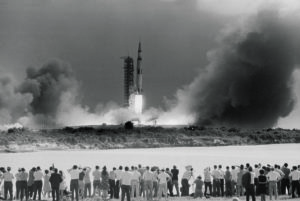 16 Jul 1969, Cape Canavaral, Florida, USA --- The Apollo 11 mission gets underway at 9:32 A.M. EDT, as the Saturn V rocket, carrying the spacecraft on its nose, blasts off. Photo shows a small part of the vast throng that flocked to Cocoa Beach to witness the spectacle seconds after ignition. Apollo 11 landed the first men on the moon. --- Image by © Bettmann/CORBIS